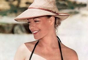 """Cheveux bien attachés et chapeau en raphia à tissage serré et larges bords, Romy a tout bon pour protéger ses cheveux du soleil ! (film : """"César et Rosalie"""")"""
